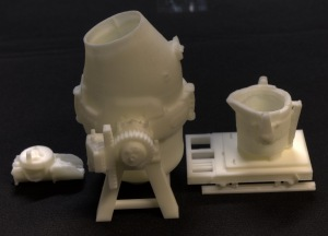 Photo showing the scale model of the melting pot exhibit, including the model of a jug on a board to one side