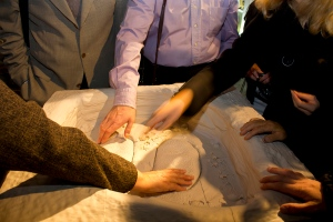Photo of  a tactile relief model being touched by different visitors